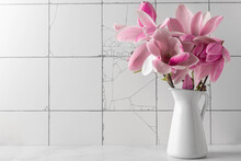 Still Life With Pink Magnolia Flowers Bouquet In Vase On White Tile Background. Wedding Or Holiday Concep