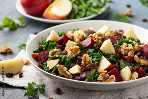 Canvas Print Kale salad with apple, beetroot, walnut and raisins in white plate
