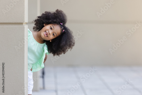Fototapeta portrait of little African American curly hair girl - hind and seek concept