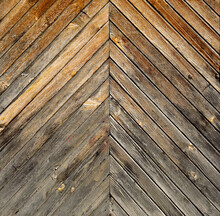 Old Wooden Surface From A Door With Oblique Boards In The Shape Of A Triangle Of Wood With Gradient Discolored Texture