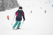 Unidentified Tourist Skiing In Flachau, The Ski Resort In Austria. Man In Grey Sportswear And With Red Bag. People On Bokeh Background. View From Behind.