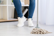 Cleaning Home. Janitor Woman. Chores Hygiene. Enjoying Result. Housework Service. Unrecognizable Woman Legs In Jeans Sneakers Shoes Staying With Mop Light Room Interior.