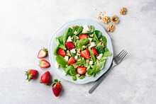 Salad With Strawberries, Feta Cheese And Walnuts. Healthy Diet Low Calorie Salad On Plate, Grey Concrete Background, Top View