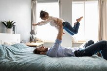 Caring Happy Young Caucasian Father Lying On Bed At Home Play With Excited Small Daughter On Family Weekend. Smiling Dad Hold Little Girl Child Engaged In Funny Game Together. Fatherhood Concept.