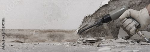 Fotografía house renovation concept, construction worker breaks the old plaster of the wall