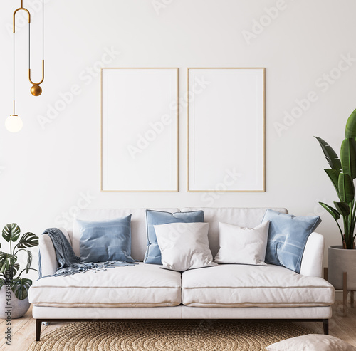 Poster mockup in bright modern room, white sofa with blue cushions and green plants on minimal background, 3d render