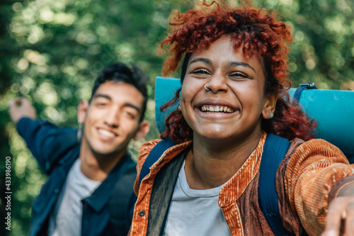 young multiethnic couple running enjoying outdoor excursion - fototapety na wymiar