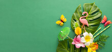 Exotic Tropical Summer Background. Summer Beach Party Concept. Pink Flamingo, Tropical Leaves, Orchid Flowers And Other Accessories On Green Background. Flat Lay, Copy Space.