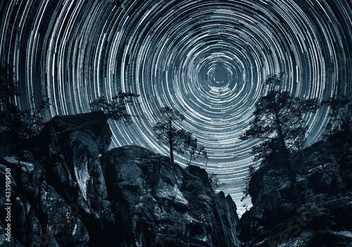 Mountains and trees on starry background with bright stars trails. Time lapse, long exposure. Elements of this image furnished by NASA. - fototapety na wymiar