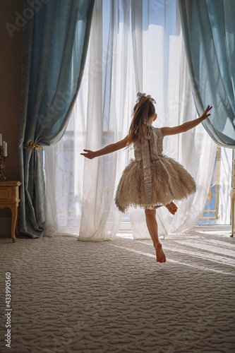 Back view of little girl in white dance dress dancing by the window in luxury apartment bedroom and looking out at the sea Fototapet