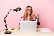 Young Student Woman In A Workplace With A Laptop Over Pink Background Pointing To The Side To Present A Product