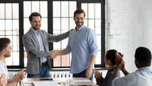Proud Boss Encouraging And Thanking Happy Employee For Good Job, Shaking Hand. Excited Worker Getting Promotion, Recognition, Respect And Applause Of Colleagues. Leader Introducing New Team Member