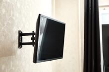 Swivel TV Bracket LED Display. Side View. X-shaped Red Fasteners. Black Color. Multiplanar. Hangs On A Wall. Reliable And Comfortable Fastening. Childproof And Rollover Protection. Metallic Equipment