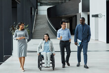Full Length View At Diverse Group Of Business People Chatting In Graphic Office Lobby While Moving Towards Camera, Focus On Smiling Young Woman In Wheelchair