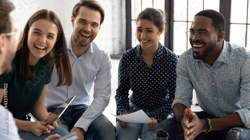 Coach or group leader telling funny story or joke to laughing diverse team. Happy multiethnic employees having fun while discussing project, sharing ideas, informal brainstorming sitting on chairs