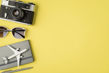 Top View Photo Of Camera Sunglasses Pen And Plane Model On Grey Notebook On Isolated Pastel Yellow Background With Copyspace