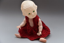 Closeup Of Creepy Old Doll In Red Dress Isolated On Gray Background