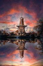 Vertical Shot Of A Windmill Reflected In A Lake With Pink And Purple Clouds Above It