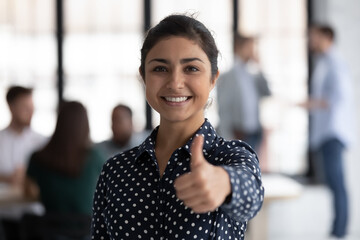 Photo portrait of happy Indian female business leader gesturing like, showing thumb up. Team working in background. Satisfied client woman gives approval positive feedback, recommends company service