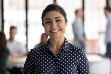 Corporate Portrait Of Happy Indian Female Business Team Leader. Millennial Employee Looking At Camera And Smiling While Group Working In Office Behind Her. Businesswoman, Leadership Concept. Head Shot