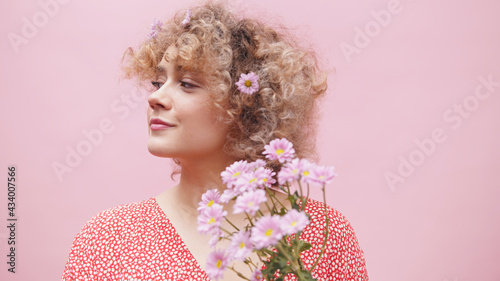 Photographie Inpatient young woman with the floral decor in her hair holding a bouquet of fresh spring purple flowers and waiting for someone