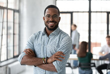 Portrait Of Happy African American Small Business Owner Posing With Hands Folded. Millennial Black Male Team Leader Smiling, Looking At Camera, Employees Working In Modern Office Behind. Head Shot