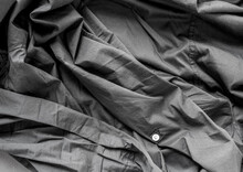 Unpressed Dark Grey Black Casual Dress Shirt With Seams - Photographed From Above With Low Or Raking Light - Emphasis On Texture And Folds