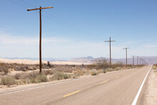 Row Of Telephone Poles Along A Road Crossing The Mojave Desert Under A Blue Sky