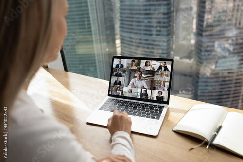 Foto Back view of businesswoman talk speak on video call on laptop in office with multiethnic partners or clients
