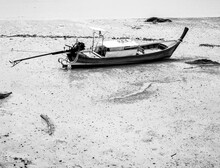 Empty Villager's Wooden Fishing Longtail Boat In The Beach Mud.