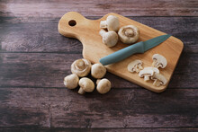 Top View Of Fresh Agaricus Bisporus Or .Champignon Mushroom With Knife On Wooden Cutting Board On Wooden Background.