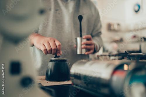 Fotografiet Barista measure coffee powder and brewing black moka coffee using moka coffee maker
