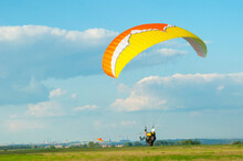 Paraglider With A Man In The Sky On The Background Of A City Landscape With Factories And A Blue Sky With Cloud