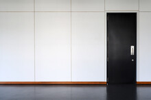 Modern Black Wooden Door Closed Shut With Metallic Handle On White Wall. Empty Room Interior. Free Space For Display Or Montage Products.