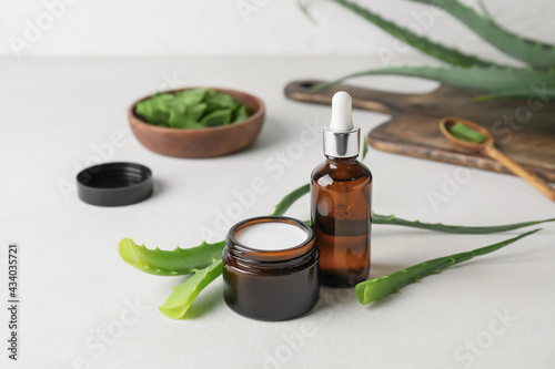 Bottle of essential oil, jar with cream and aloe pieces on light background - fototapety na wymiar