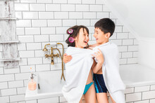 The Children Wrapped Themselves In A White Towel In The Bathroom And Had Fun.