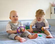 Cute Little Children Infant Boy And Toddler Girl Having Fun While Playing With Toy Construction Set On Bed At Home. Playtime For Curious Brother And Sister In Bedroom. Family Spending Time Together