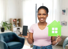 Eco Living, Environment And Sustainability Concept - Happy Smiling Young African American Woman Holding Smartphone And Green House Over Home Room Background