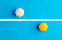 White And Orange Table Tennis Balls Are Opposed To Each Other Divided By A Line On Blue Background.