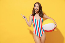 Happy Young Woman Slim Body Wear Striped Red Blue One-piece Swimsuit Hold Play Inflatable Beach Ball Isolated On Vivid Yellow Color Wall Background Studio. Summer Hotel Pool Sea Rest Sun Tan Concept.