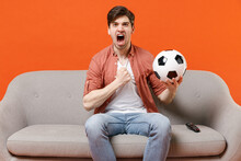 Young Desperate Expressive Man Football Fan In Shirt Support Team With Soccer Ball Sit On Sofa At Home Watch Tv Live Stream Clench Fist Scream Shout Isolated On Orange Background People Sport Concept.