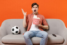 Young Indignant Man Football Fan In Shirt Support Team With Soccer Ball Sit Sofa Home Watch Tv Eat Snack Hold Takeaway Pop Corn Bucket Spread Hand Isolated On Orange Backgrounds People Sport Concept.