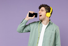 Young Singer Man 20s Wear Casual Green Mint Shirt White T-shirt Yellow Headphones Singing Song In Microphone Mobile Cell Phone Record Voice By Dictaphone Isolated On Purple Background Studio Portrait.