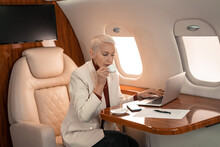 Businesswoman Drinking Coffee And Using Laptop Near Document In Plane