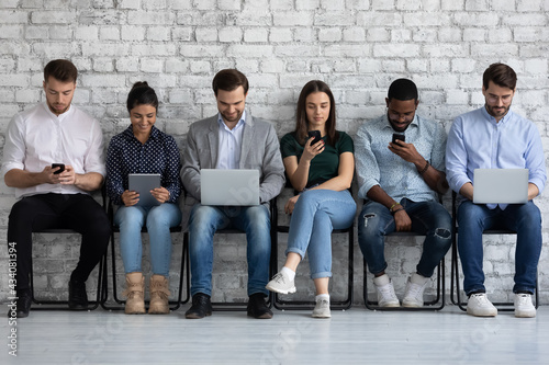 Fototapeta Diverse group of millennial people focused on different devices, sitting together in row, using phones and computers, checking social media news, chatting online in silence