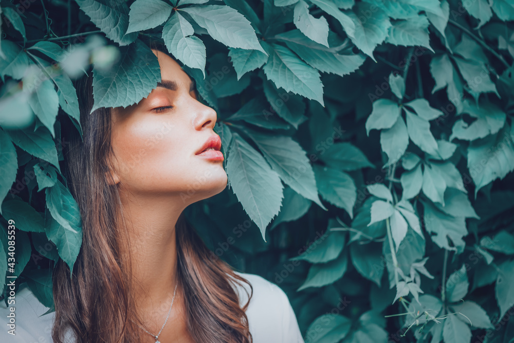 Beautiful fashion model girl enjoying nature, breathing fresh air in summer garden over Green leaves background. Harmony concept. Healthy beauty woman outdoor portrait - obrazy, fototapety, plakaty