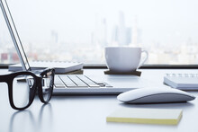 Modern Desktop With Open Laptop, Coffee Mug, Paper Stick Notes And Glasses On White Table On Megapolis City Background.