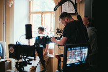 Director Of Photography With A Camera In His Hands On The Set. Professional Videographer At Work On Filming A Movie