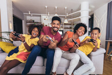 African American Family Playing Video Games Together And Having Fun At Home