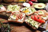 Fototapeta Kawa jest smaczna - Different delicious sandwiches with microgreens on wooden board
